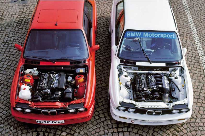 Two BMW M3s with popped hoods, E30 engine