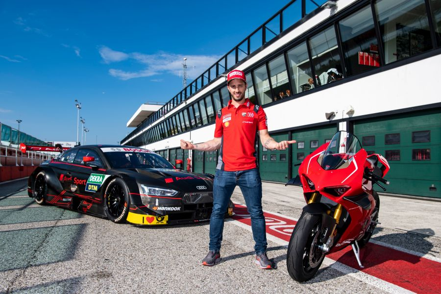 Andrea Dovizioso next to his Ducati Panigale V4 R and Audi RS 5 DTM