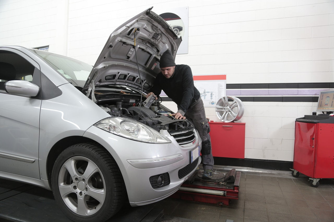 Car Mechanic Working Under The Hood Of A Silver Car